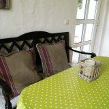 Große Holzbank mit einem Tisch und fgiftgrüner Tischdecke