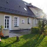 Saftige grüne Wiese grenzt an die Terrasse des Hauses