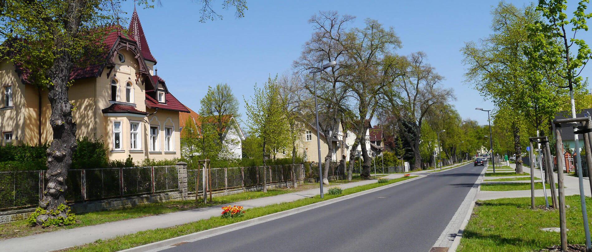 Straße mit Grünstreifen und verschiedenen Villen