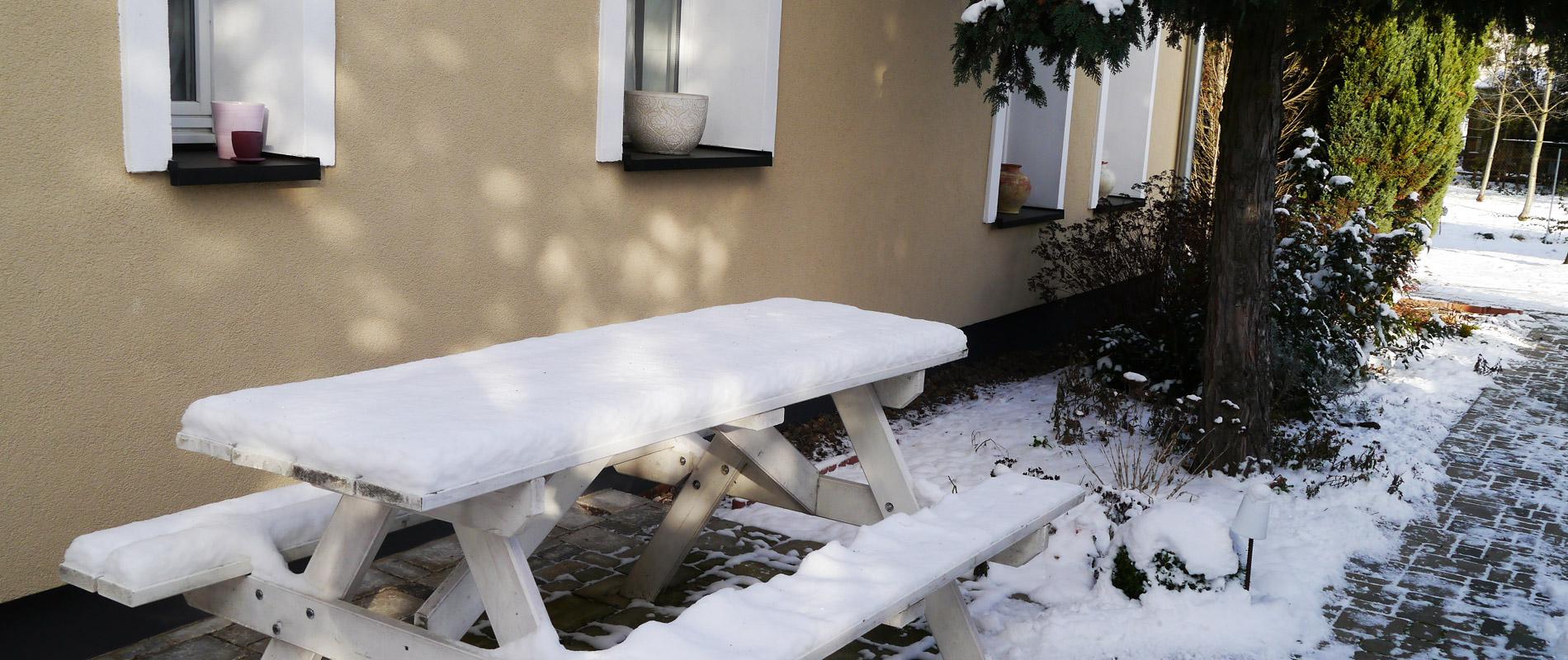 Ferienwohnung im Winter mit Bank vor dem Haus